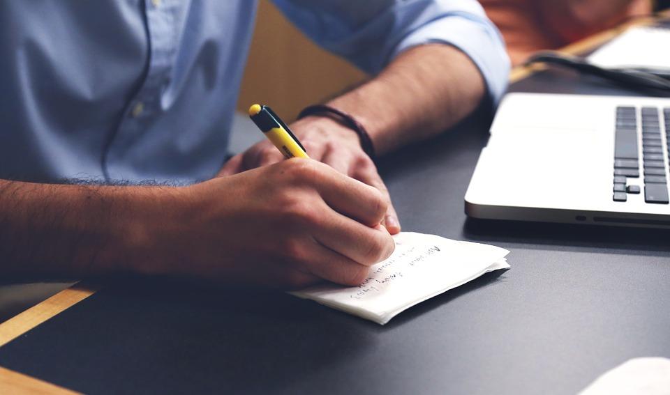 Mand skriver noter